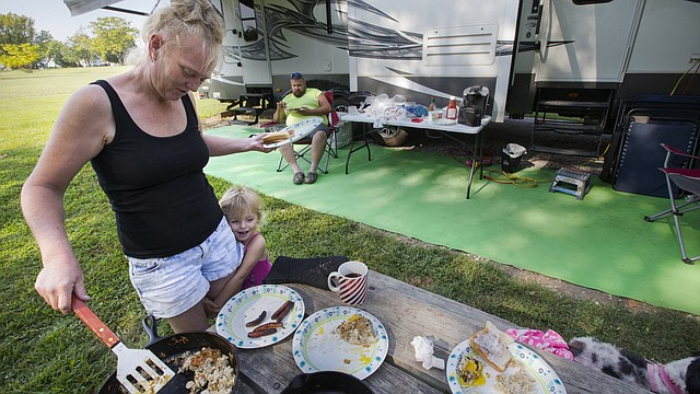 Jennifer Oliver, Topeka, dishes out breakfast as her 3-year-old granddaughter Kaelyn Tanner hangs onto her leg on Friday, Sept. 1, 2017 at Clinton Lake State Park. In back is Adrian Oliver. The three and others with their group were prepared for a weekend of camping over the Labor Day holiday. All camping spots with electrical outlet access were booked to capacity as of Friday morning as weekend campers like the Olivers had begun to arrive.