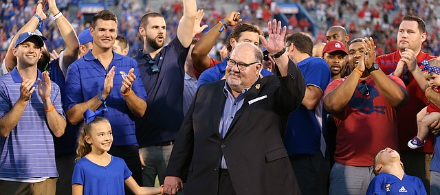 Former Kansas head football coach Mark Mangino and members of the 2008 Orange Bowl team wave to fans as they are recognized during a halftime ceremony, Saturday, Sept. 2, 2017 at Memorial Stadium.