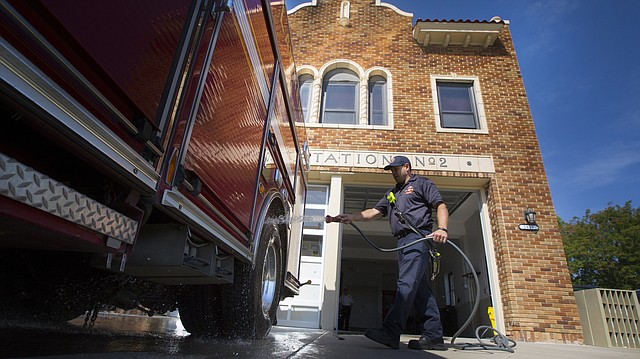 Capt. Brandon Holloman sprays down Engine No. 1 on Thursday, Aug. 24, 2017, at the original Fire Station No. 2, a 1932 building near 19th and Massachusetts streets. The ambulance from Fire Station 1 on Kentucky Street and its crew will be housed at the old station for eight to 12 months while Station 1 is renovated.