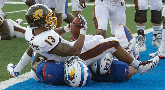 Central Michigan running back Devon Spalding (13) lands on two KU defender after scoring a touchdown in CMU's win over KU Saturday, Sept. 9 at Memorial Stadium.