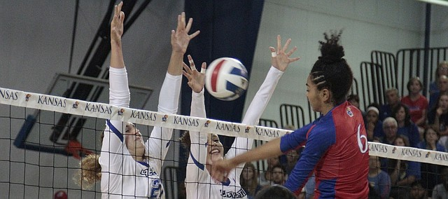 Kansas sophomore Zoe Hill hits the ball into Creighton's block, which was set by freshman Naomi Hickman (21, a Free State alumna) and junior Jaali Winters (5), in the second set of the Jayhawks' 25-20, 25-16, 29-27 loss to the Bluejays on Saturday in the Horejsi Family Athletics Center.