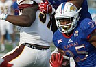 Kansas running back Dom Williams (25) squeezes between blocks in a run during the Jayhawks game against Central Michigan Saturday, Sept. 9 at Memorial Stadium.
