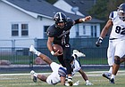 Lawrence High senior quarterback Dante Jackson (1) breaks a tackle against Lee's Summit West on Friday at LHS.