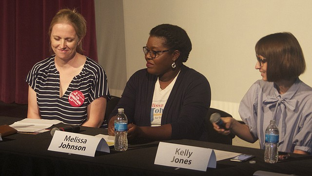 Lawrence school board candidate Kelly Jones, right, passes the microphone Saturday at a Lawrence school board candidate forum at the Lawrence Arts Center. Also at the table were Kathleen Gordon-Ross, filling in for her husband, candidate Ronald Gordon-Ross, and incumbent Melissa Johnson. The other four candidates did not attend the forum.