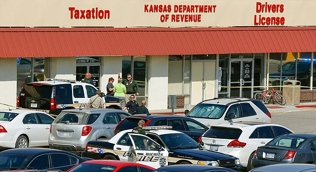 In this Tuesday, Sept. 19, 2017 photo, police investigate the shooting of a Kansas Department of Revenue employee in Wichita, Kan. (Fernando Salazar /The Wichita Eagle via AP)