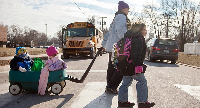 In this photo from Jan. 14, 2015, Amanda Bryson walks home from Woodlawn Elementary School with her daughter Arianna, 7. Bryson was also pulling a wagon with her 4-year-old twins, Sasha and Trenton.