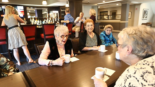 Margaret Seal leans across the table to talk with LaDonna Laing as the two and other residents at Pioneer Ridge Independent Living pub, 1000 Wakarusa, enjoy a bourbon and cider within the retirement community's pub on Friday, Sept. 22, 2017.