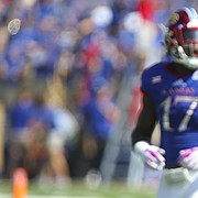 Frustrated, Kansas safety Mike Lee pulls off his helmet as he makes his way to the sidelines after a West Virginia touchdown during the second quarter on Saturday, Sept. 23, 2017 at Memorial Stadium.
