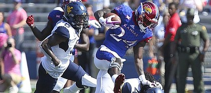 Kansas running back Taylor Martin (24) pushes off of West Virginia cornerback Mike Daniels Jr. (4) on a run during the second quarter on Saturday, Sept. 23, 2017 at Memorial Stadium.