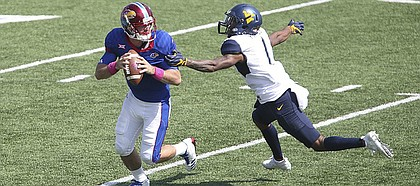 Kansas quarterback Peyton Bender (7) rolls out to pass as he is pressured by West Virginia safety Derrek Pitts (1) during the fourth quarter on Saturday, Sept. 23, 2017 at Memorial Stadium.