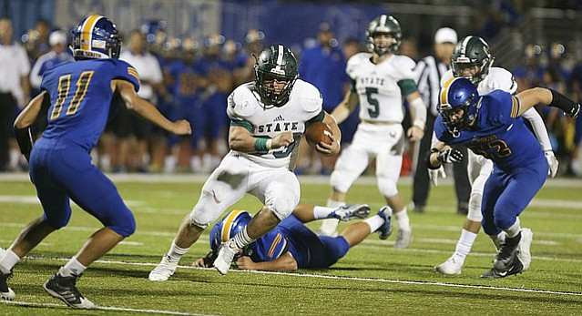 Free State running back Jax Dineen cuts through several Olathe South defender to put the ball near the goal line setting up a Firebird touchdown during the second quarter on Thursday, Sept. 28, 2017 at Olathe District Activity Center.