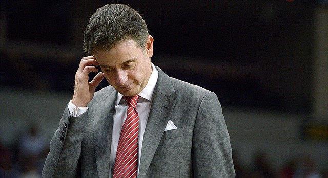 In this Dec. 31, 2013, file photo, Louisville head coach Rick Pitino walks in front of the bench during the second half of an NCAA college basketball game against Central Florida in Orlando, Fla. Louisville announced Wednesday, Sept. 27, 2017, that they have placed basketball coach Rick Pitino and athletic director Tom Jurich on administrative leave amid an FBI probe. (AP Photo/Phelan M. Ebenhack, File)