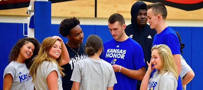 KU men's basketball players (left to right) Devonte' Graham, Clay Young, Udoka Azubuike and Mitch Lightfoot huddle alongside a group of Rock Chalk Dancers in preparation for Late Night in the Phog.