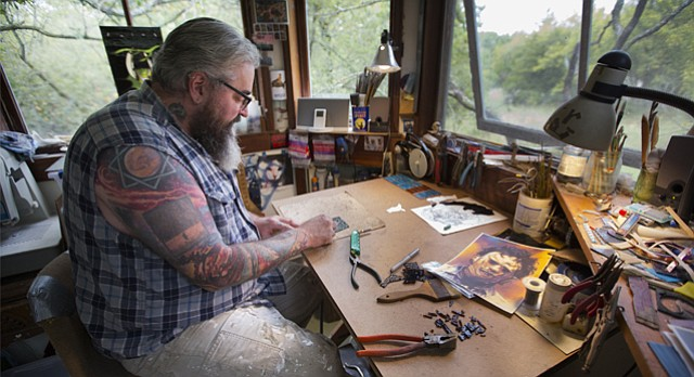 "Stained-glass artist John Niswonger works to cut glass pieces for a ""Texas Chainsaw Massacre"" sun catcher ordered from a buyer in Canada, Tuesday, Sept. 26, 2017 in the studio of his Lake Dabinawa home."