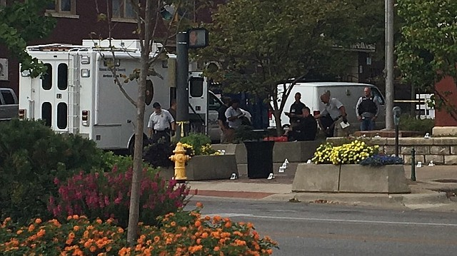 Forensic investigators work Sunday morning on the corner of 11th and Massachusetts streets next to Watkins Community Museum. About 11:30 a.m., the street was still blocked off to traffic after a shooting about 10 hours earlier left three people dead and others injured.