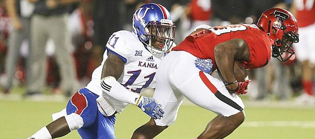 Kansas linebacker Mike Lee (11) tries to bring down Texas Tech wide receiver Cameron Batson (13) during the third quarter on Thursday, Sept. 29, 2016 at Jones AT&T Stadium in Lubbock, Texas.