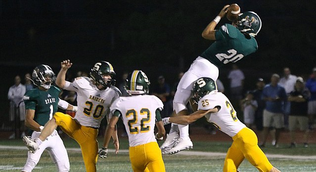 Free State wide receiver Jaxson Webb (20) jumps above defender to catch a pass during the Firebirds game against Shawnee Mission South Friday evening at FSHS.