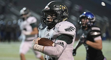 Free State senior quarterback Gage Foster runs down the sideline on his way to a touchdown against Olathe Northwest on Thursday at College Boulevard Activity Center.