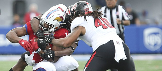 Kansas running back Khalil Herbert (10) is stopped short of a first down by Texas Tech linebacker Dakota Allen (40) and another Red Raider player during the first quarter on Saturday, Oct. 7, 2017 at Memorial Stadium.