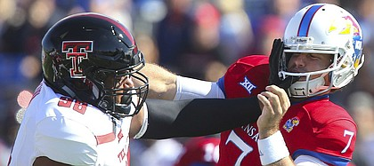 Texas Tech defensive lineman Nick McCann (98) gives a slap to Kansas quarterback Peyton Bender (7) after a pass during the first quarter on Saturday, Oct. 7, 2017 at Memorial Stadium.