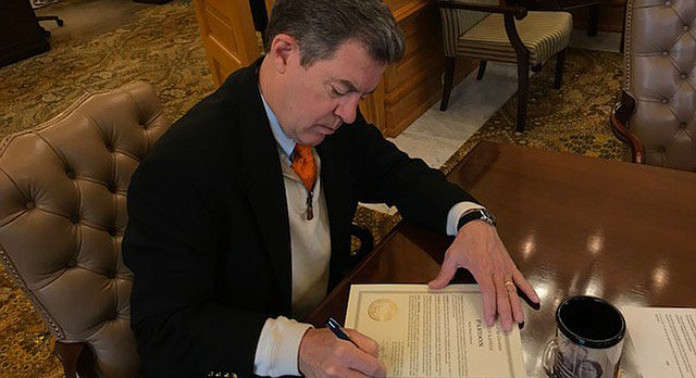 Gov. Sam Brownback signs an executive pardon for Mark Schmitt, who was convicted of felony theft in 1994, on Tuesday, Oct. 10, 2017.