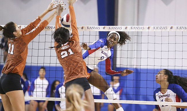 Kansas middle blocker Mmachi Nwoke (9) has a shot blocked by Texas outside hitter Lexi Sun (11) and Texas middle blocker Chiaka Ogbogu (21) during the second set on Wednesday, Oct. 11, 2017 at Horejsi Center.