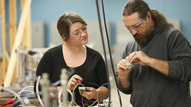 Industrial Engineering Technology classmates Lindsay Hamm and Andrew Wilkins work together to assemble and test the various relay switches and air valves of an automatic drill press they are building on Thursday, Oct. 12, 2017 at Peaslee Tech, 2920 Haskell Ave. Hamm is one of ten female students at Peaslee enrolled in the Growing Real Opportunities for Women (GROW) program at Peaslee Tech, which was recently awarded a $40 thousand grant from AT&T.