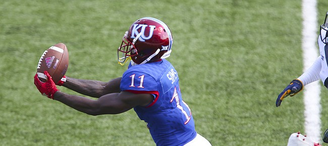 Kansas wide receiver Steven Sims Jr. (11) catches a deep pass beyond West Virginia cornerback Mike Daniels Jr. (4) to set up a KU touchdown during the third quarter on Saturday, Sept. 23, 2017 at Memorial Stadium.