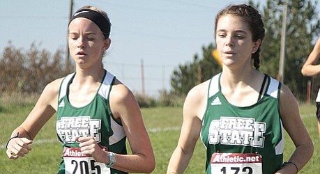 Free State sophomore Emily Stone, left, and junior Erin Fagan, right, run side by side during the first mile of the Sunflower League meet on Friday at Rim Rock Farm.