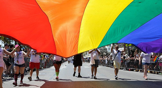 Participants carry a rainbow flag during a parade along Ocean Drive at Miami Beach Gay Pride, Sunday, April 10, 2016, in Miami Beach, Fla. (AP Photo/Lynne Sladky)