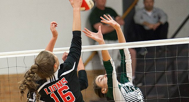 Lawrence High junior Brooke Wroten (13) and senior Katelyn Mask (16) jump up for a block as Free State sophomore Mya Gleason sets the ball during the City Showdown dual Tuesday, Oct. 17, 2017 at LHS.