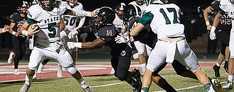Free State senior quarterback Gage Foster puts a stiff arm on Lawrence High linebacker Ja'Relle Dye (14) during the second quarter of the City Showdown on Friday, Oct. 20, 2017 at LHS.