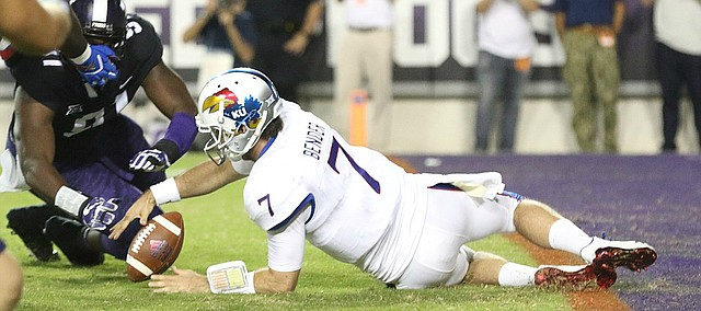 Kansas quarterback Peyton Bender (7) recovers a fumbled snap before TCU defensive tackle L.J. Collier (91) during the second quarter, Saturday, Oct. 21, 2017 at Amon G. Carter Stadium in Fort Worth.