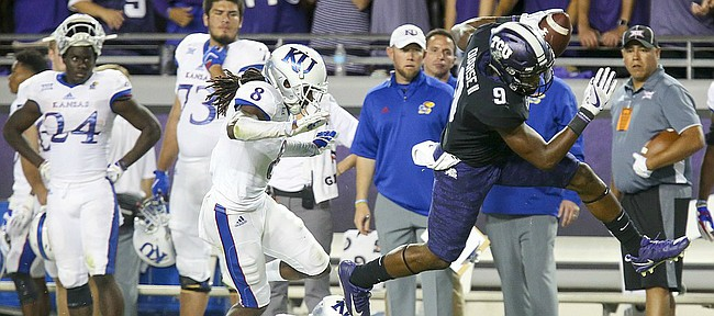 TCU wide receiver John Diarse (9) escapes Kansas cornerback Shakial Taylor (8) and Kansas safety Mike Lee (11) for a touchdown during the second quarter, Saturday, Oct. 21, 2017 at Amon G. Carter Stadium in Fort Worth.