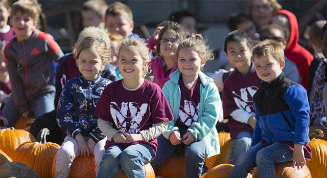 Kindergartners from Northview Elementary in Olathe squat down on a gathering of pumpkins for a class picture following a tour at Schaake's Pumpkin Patch, 1791 North 1500 Road, on Tuesday, Oct. 17, 2017.