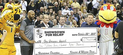 Kansas head coach Bill Self, Missouri head coach Cuonzo Martin, left, Missouri athletic director Jim Sterk and Kansas athletic director Sheahon Zenger hold a ceremonial check for $1.75 million raised for hurricane relief from the Showdown for Relief exhibition, Sunday, Oct. 22, 2017 at Sprint Center in Kansas City, Missouri.