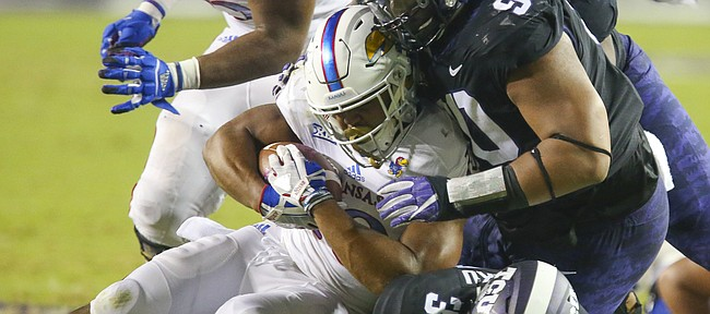 Kansas running back Khalil Herbert (10) is driven to the ground by TCU defensive tackle Ross Blacklock (90) and TCU safety Ridwan Issahaku (31) during the second quarter, Saturday, Oct. 21, 2017 at Amon G. Carter Stadium in Fort Worth.