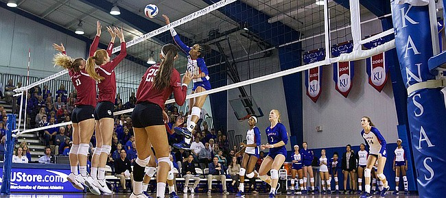 Kansas sophomore Zoe Hill drills a spike over three Oklahoma blockers on Wednesday, Oct. 25, 2017 at Horejsi Family Athletics Center.