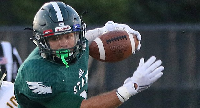 Free State's Bo Miller (9) eludes a Shawnee Mission South defender during the Firebirds game against SMS Friday evening at FSHS.