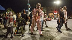 Zombies, including Juliet Green, of Lawrence, shamble across 8th and Massachusetts streets during the 10th annual Zombie Walk on Oct. 20, 2016.