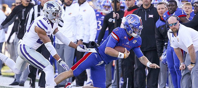 Kansas quarterback Carter Stanley (9) is shoved out of bounds by Kansas State defensive back Denzel Goolsby (20) during the third quarter on Saturday, Oct. 28, 2017 at Memorial Stadium.
