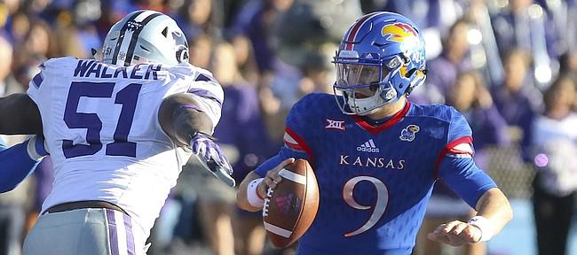 Kansas quarterback Carter Stanley (9) tries to escape Kansas State defensive end Reggie Walker (51) during the third quarter on Saturday, Oct. 28, 2017 at Memorial Stadium. At left is Kansas offensive lineman Hakeem Adeniji (78).