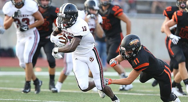 Lawrence High receiver Ekow Boye-Doe escapes Shawnee Mission Northwest defensive back Mark Addington as he runs for a touchdown during the first quarter on Thursday, Aug. 31, 2017 at Shawnee Mission North District Stadium.