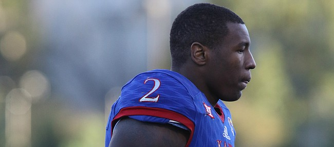 Injured Kansas defensive end Dorance Armstrong Jr. (2) walks to the sidelines after a team huddle during the fourth quarter on Saturday, Oct. 28, 2017 at Memorial Stadium.