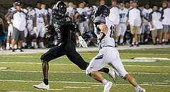Lawrence Highs senior receiver Ekow Boye-Doe tries to shake a tackler from Lee's Summit West on Friday at LHS.