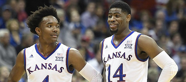 Kansas sophomore guard Malik Newman (14) smiles with senior Devonte' Graham (4) during a free throw Tuesday in an exhibition game vs. Pittsburg State at Allen Fieldhouse.