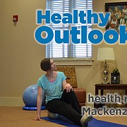 Becky Bridson, a Lawrence-based Yamuna body rolling practitioner, guides Journal-World health reporter Mackenzie Clark through rolling the right side of her back on the silver ball.