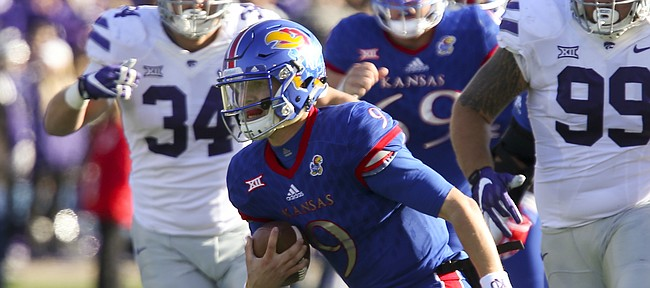 Kansas quarterback Carter Stanley (9) escapes on a run during the second quarter on Saturday, Oct. 28, 2017 at Memorial Stadium.