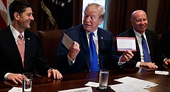 President Donald Trump holds an example of what a new tax form may look like during a meeting on tax policy with Republican lawmakers in the Cabinet Room of the White House, Thursday, Nov. 2, 2017, in Washington. From left, Speaker of the House Rep. Paul Ryan, R-Wis., Trump, and Chairman of the House Ways and Means Committee Rep. Kevin Brady, R-Texas. (AP Photo/Evan Vucci)