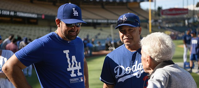 Los Angeles Dodgers' Adrian Gonzalez, left, and manager Dave Roberts, center, talk with 100-year-old fan Bob Logsdon before a baseball game against the Colorado Rockies, Saturday, Sept. 9, 2017, in Los Angeles. (AP Photo/Michael Owen Baker)